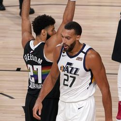 Denver Nuggets' Jamal Murray (27) keeps his arms in position as Utah Jazz's Rudy Gobert (27) walks past after Gobert scored a basket and drew a foul on the play during the second half an NBA first round playoff basketball game, Tuesday, Sept. 1, 2020, in Lake Buena Vista, Fla.