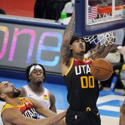Utah Jazz guard Jordan Clarkson (00) dunks in front of teammate Rudy Gobert, left, and Oklahoma City Thunder guard Luguentz Dort, back left, during the first half of an NBA basketball game in Oklahoma City, Monday, Dec. 28, 2020.
