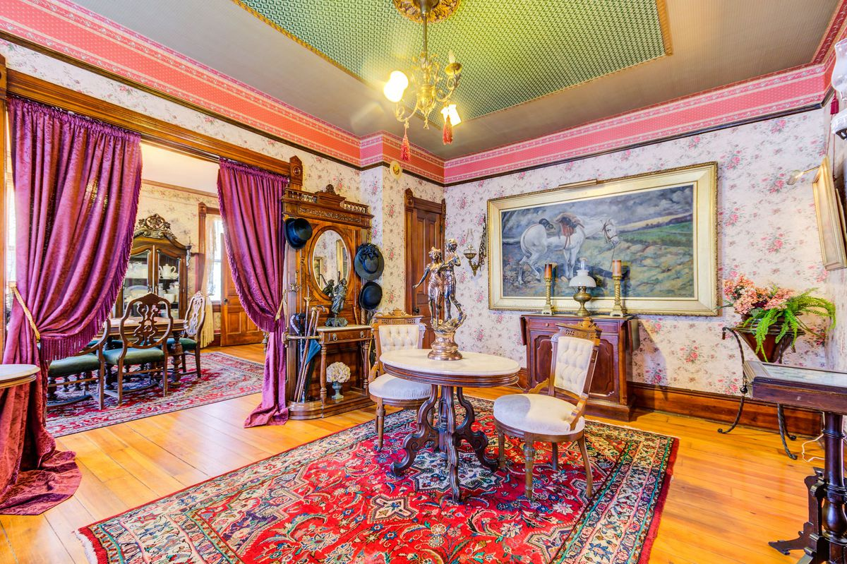 A living room with a red Oriental rug, a two-person table, floral wallpaper, and lots of Victorian trinkets.