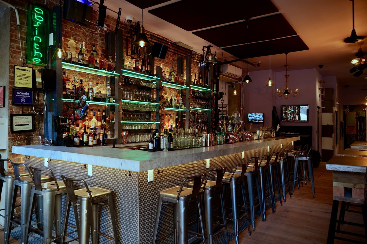 An interior restaurant photo focusing on a backlit bar with alcohol lining the shelves and backless stools set up around the outer perimeter of the bar