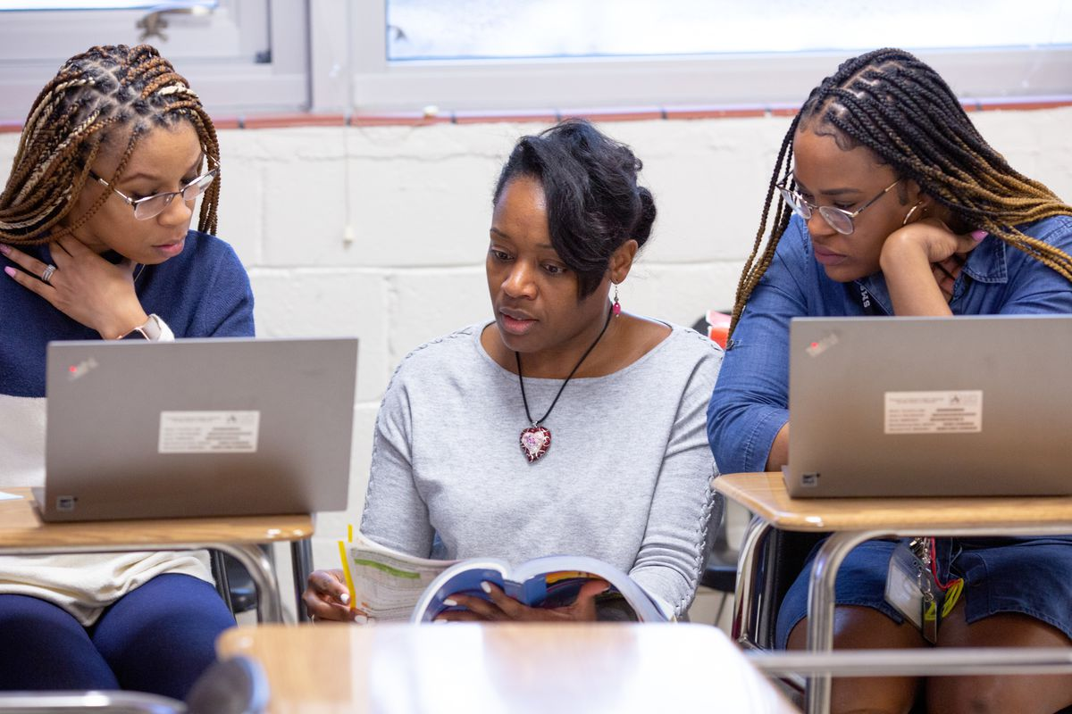 Two young women sit at desks in a classroom with laptops open, looking to a teacher who sits between them going through a textbook.