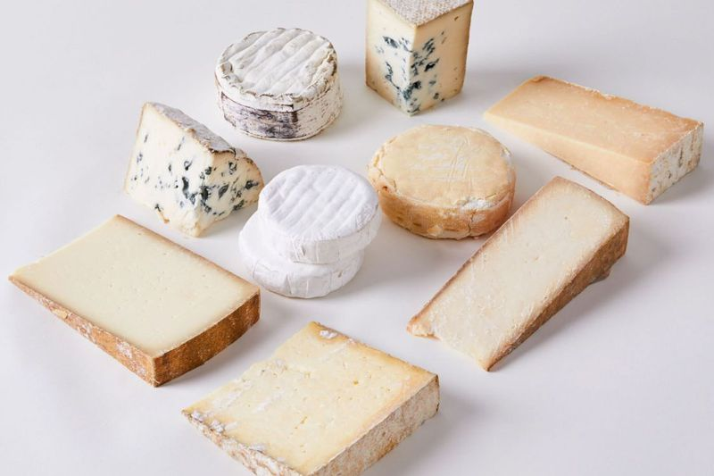 An assortment of cheese, including wedges and rounds of soft cheese