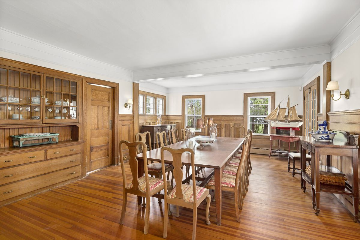A dining room with a large wooden table and chairs, a hutch, and white ceiling.
