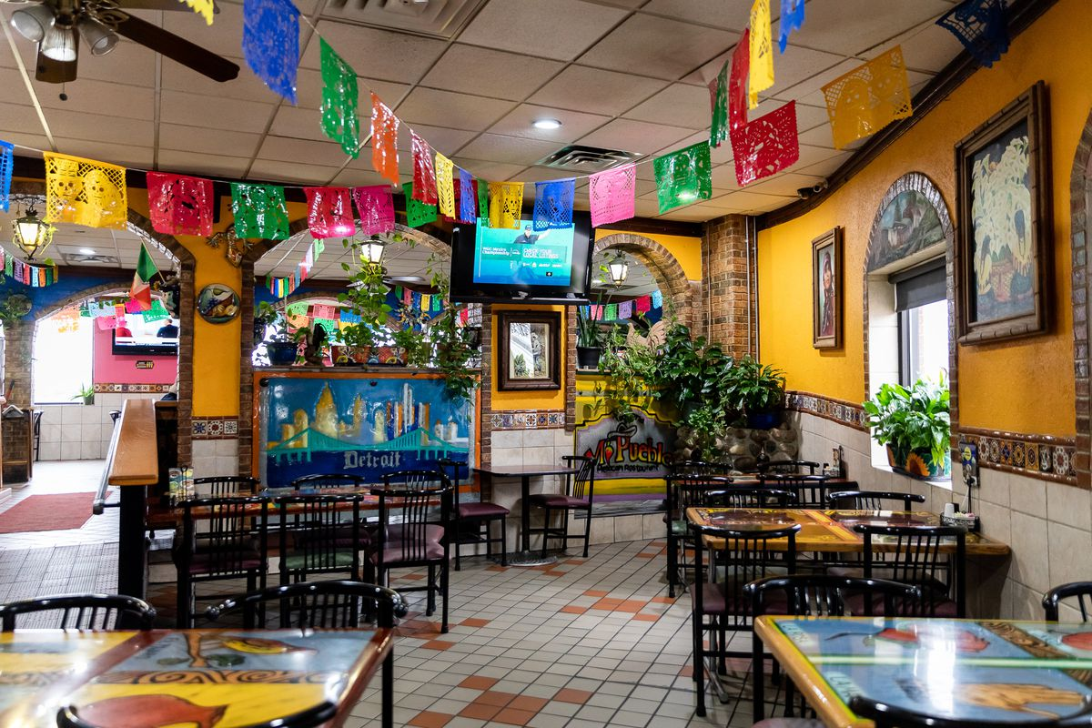 The colorful dining room at Taqueria Mi Pueblo features multi-colored flags on strings hanging from the ceiling.