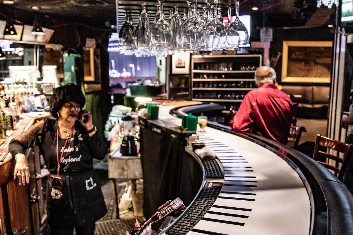 A bartender in a hat answers the phone behind the curvy piano topped bar at Baker's.