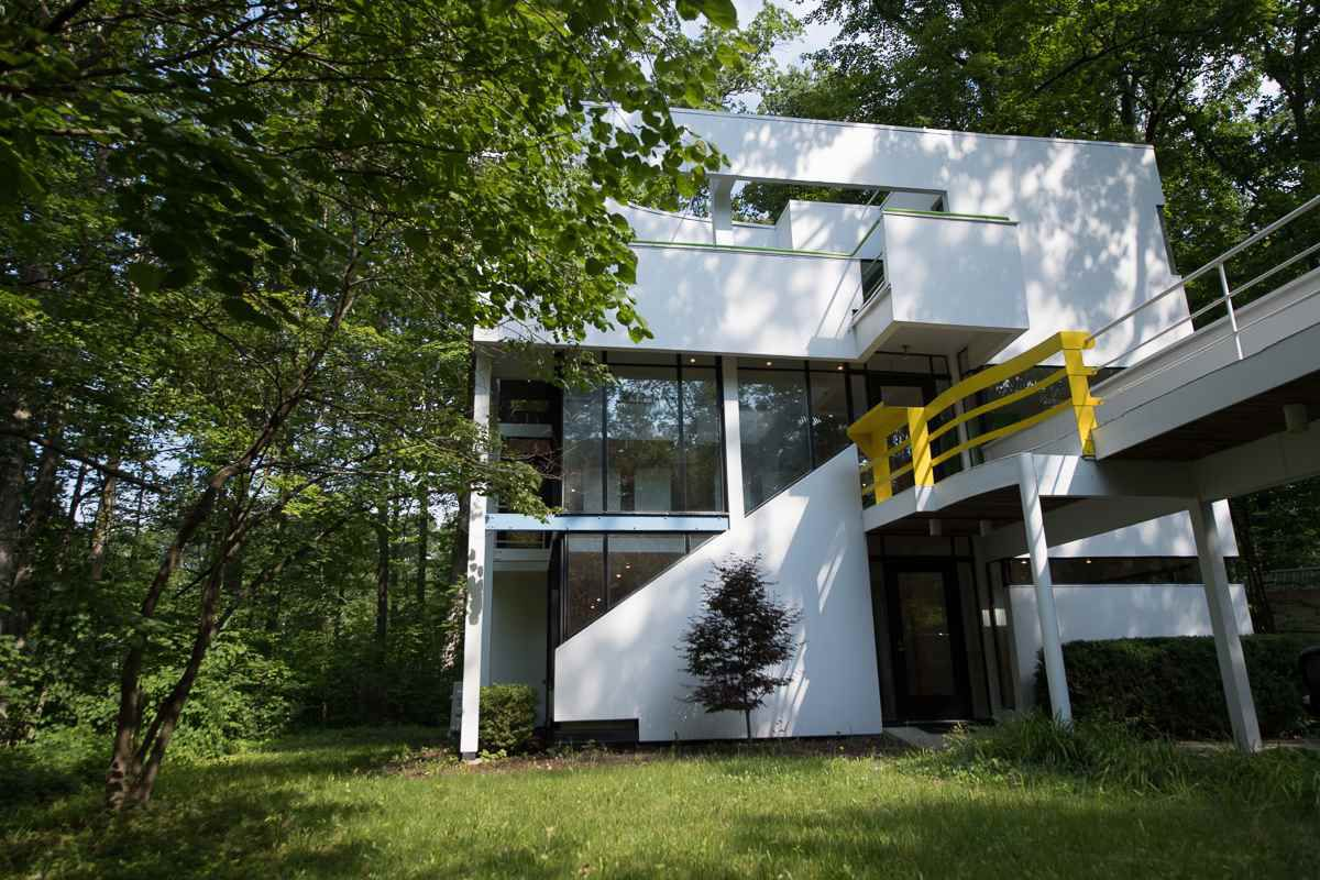 Shot of boxy and white modern home with balconies and glass expanses set on a woodsy site.