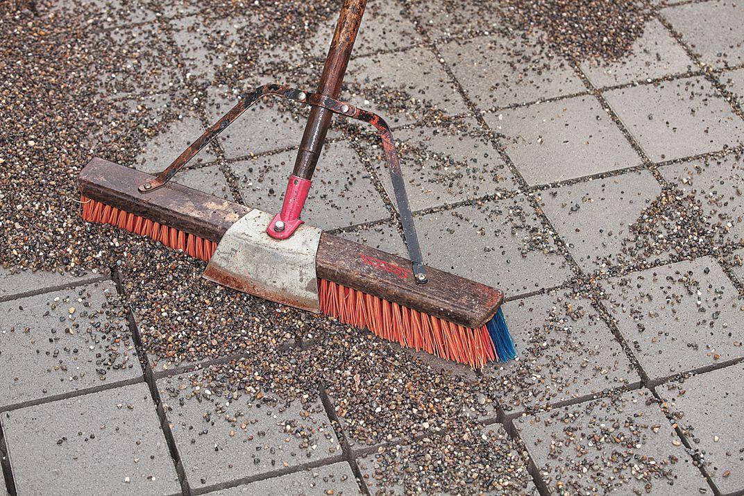 Sweeping Permeable Stones Into Gaps Of Pavers With Wide Broom