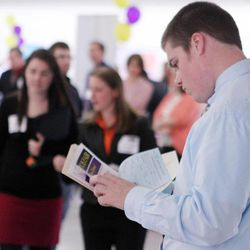 In this April 4, 2012, file photo, Scott Richards of Saint Anselm College looks over possible jobs during a career fair for college students in Manchester, N.H.