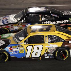 Kyle Busch (18) and Tony Stewart (14) battle side-by-side in Turn 4 during the NASCAR Sprint Cup Series auto race at Richmond International Raceway in Richmond, Va., Saturday, April 28, 2012.  Busch won the race.
