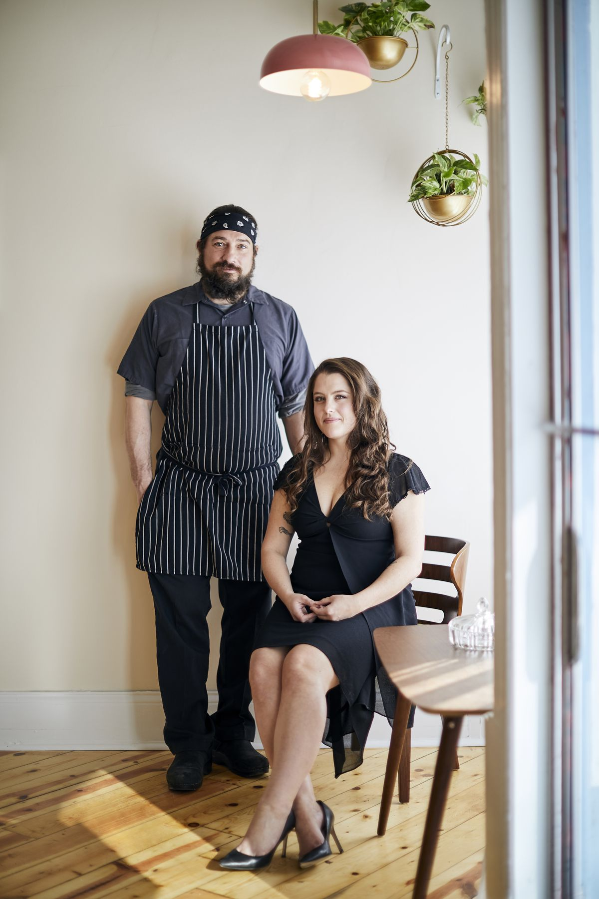 A male chef stands behind a woman who is seated