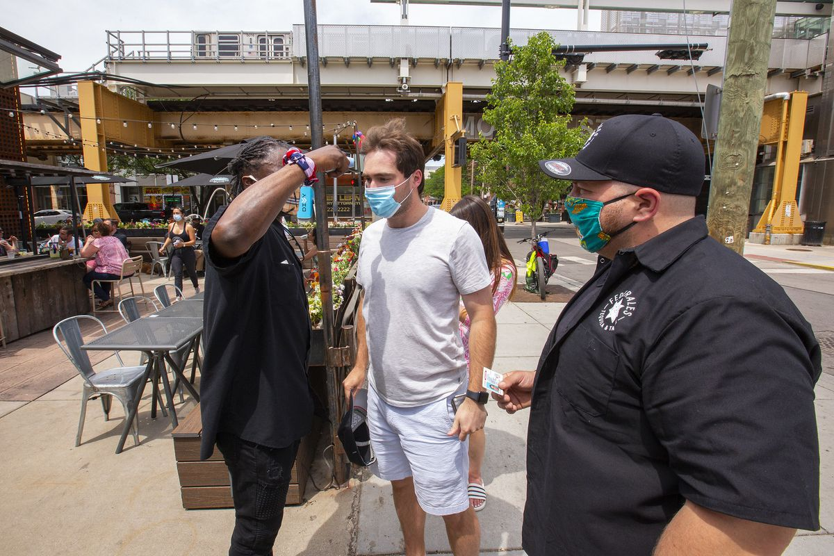 A bar worker outside using a handheld temperature reader on a masked customer waiting in line.