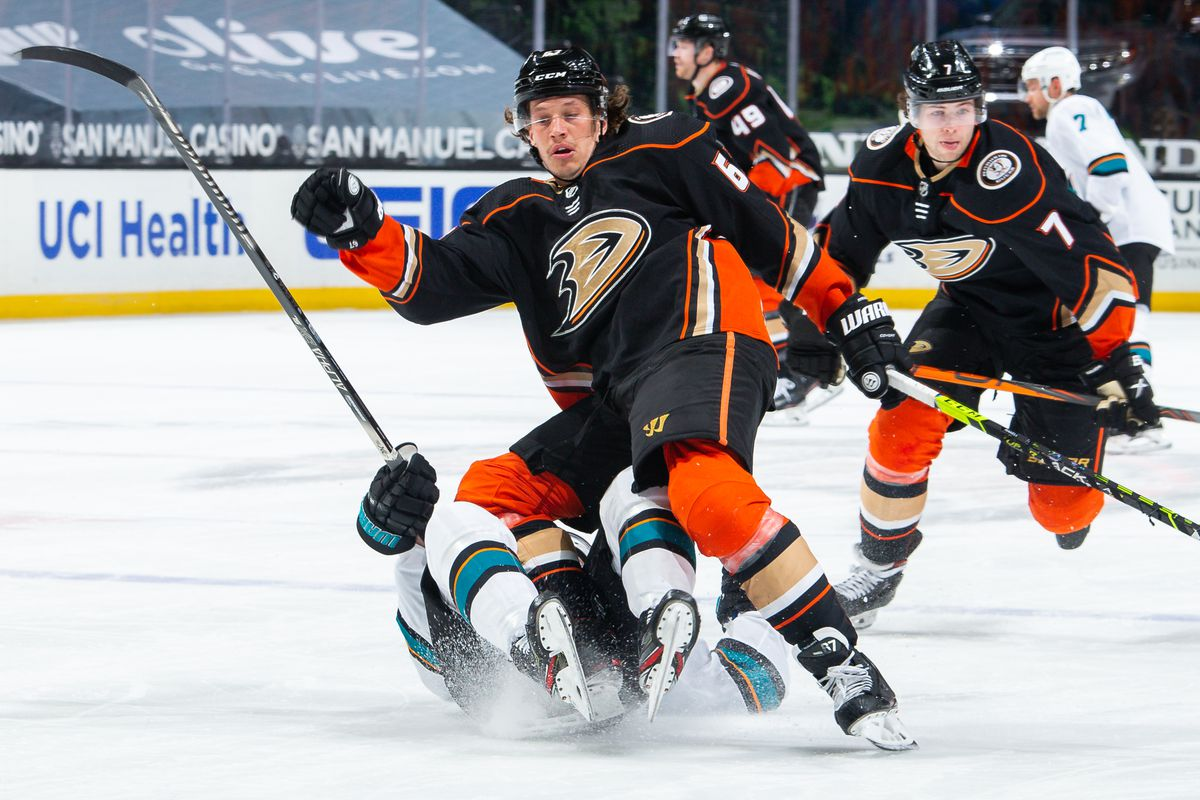 Rickard Rakell #67 of the Anaheim Ducks collides with Ryan Donato #16 of the San Jose Sharks as Ben Hutton #7 of the Anaheim Ducks skates past during the third period of the game at Honda Center on March 12, 2021 in Anaheim, California.