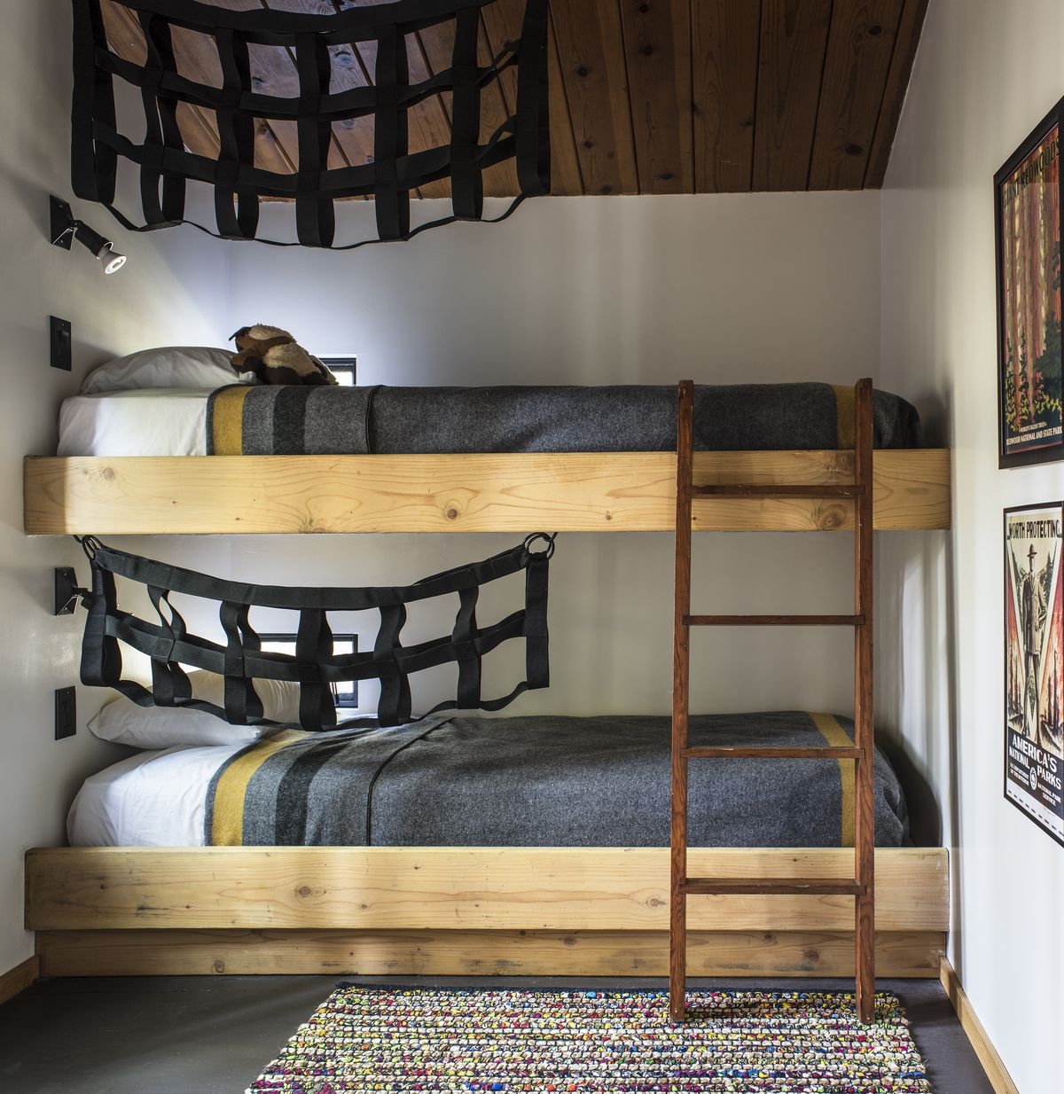 Bunk beds have cargo nets hanging to the side. They are dressed with army-style blankets.