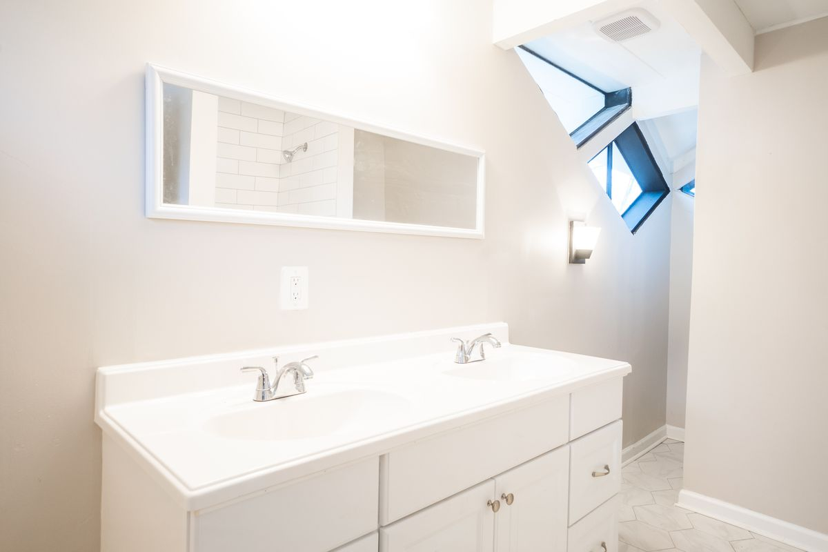 Two white sinks against a wall with a long rectangular mirror.