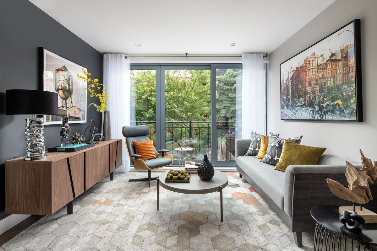 A living room with a door that leads to a balcony, a grey couch, and a round coffee table.
