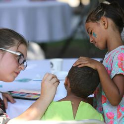 Volunteer Reese Reynolds paints the face of Jamela and Laila as homeless residents are treated to a picnic lunch in Pioneer Park in Salt Lake City on Sunday, Aug. 27, 2017. Participants also received a new blanket and listened to live music.