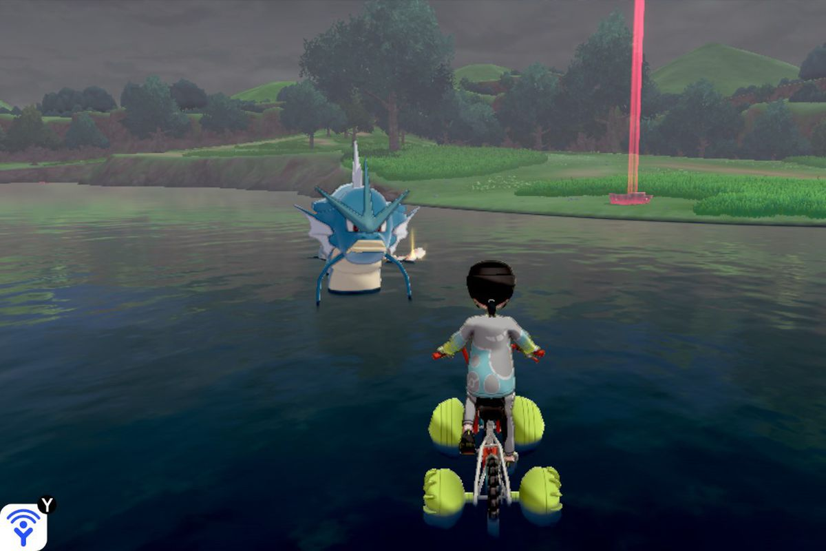 A Gyarados stares at a Pokémon trainer riding a bike in the water