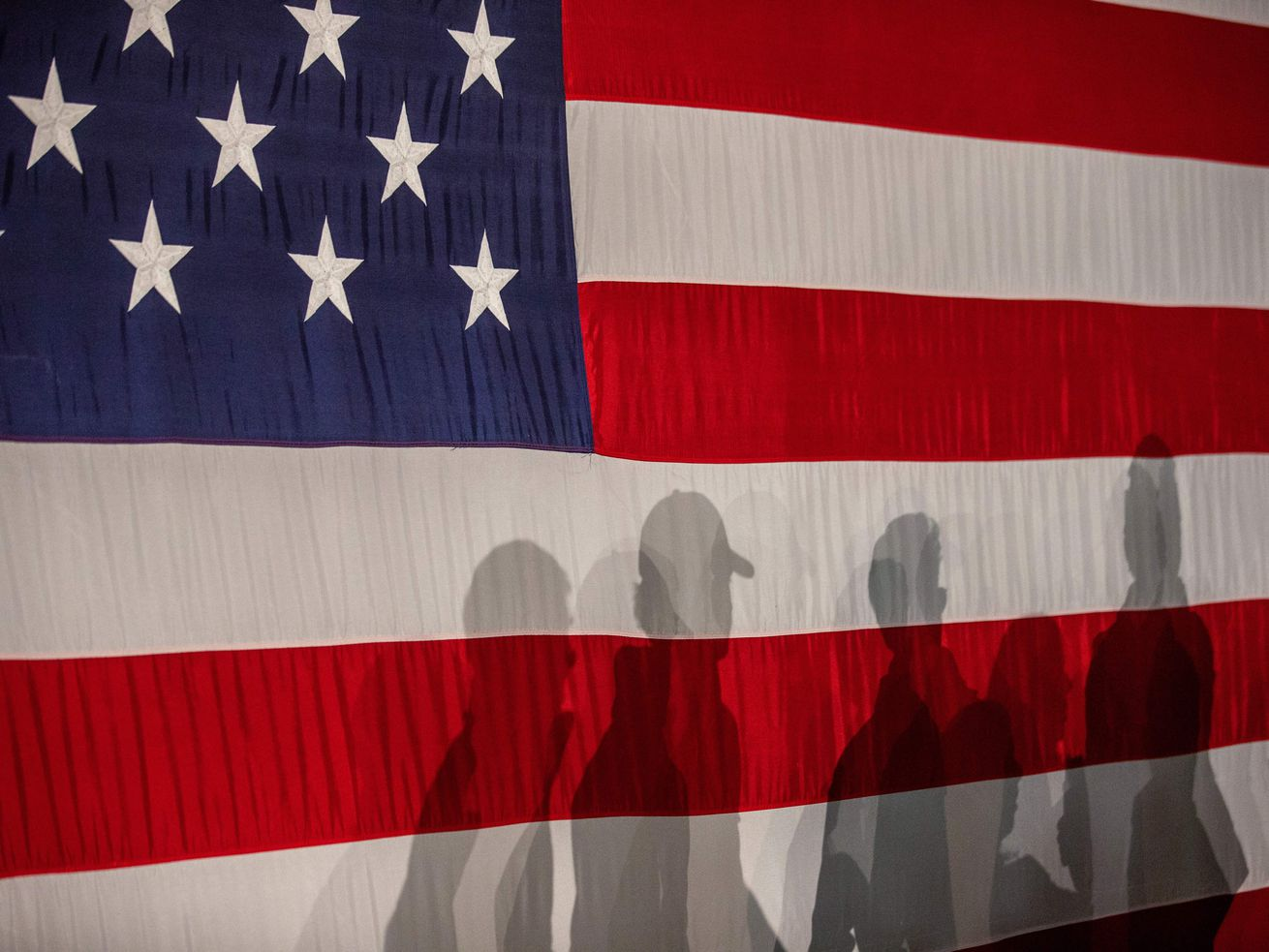 The shadows of people on an American flag backdrop.