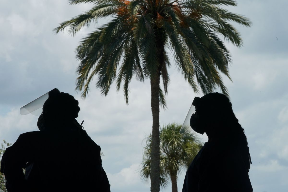 Two medical workers in silhouette at an outdoor Covid testing facility with palm trees in the background.