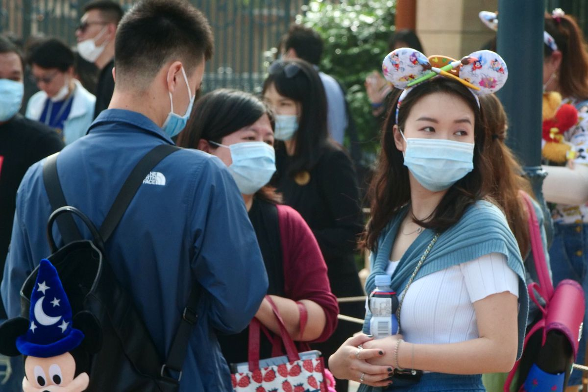 Visitors, wearing face masks, wait to enter the Disneyland theme park in Shanghai as it reopened, Monday, May 11, 2020. Visits will be limited initially and must be booked in advance, and the company said it will increase cleaning and require social distancing in lines for the various attractions. (AP Photo/Sam McNeil)