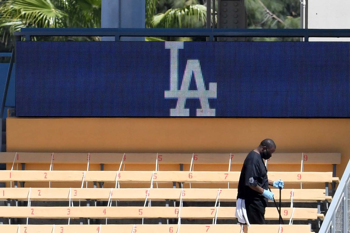 A Dodgers employee cleans the bleachers in Chavez Ravine prior to a game