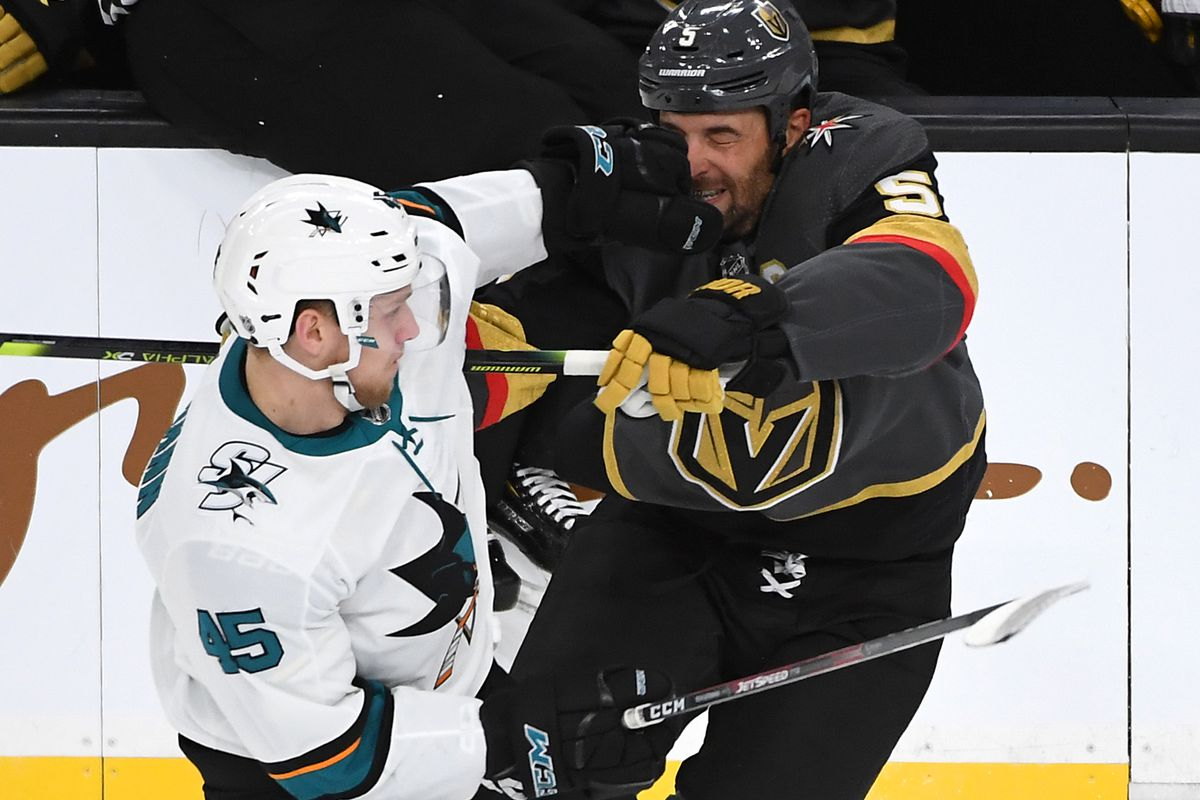 Oct 2, 2019; Las Vegas, NV, USA; Vegas Golden Knights defenseman Deryk Engelland (5) takes a glove to the face from San Jose Sharks center Lean Bergmann (45) during the third period at T-Mobile Arena.