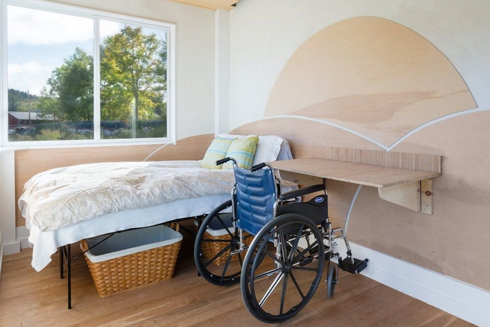 The interior of a tiny house. There is a bed, storage baskets, a shelf, and a window. There is a blue wheelchair next to the bed.