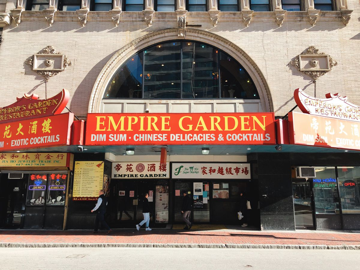 The facade of Empire Garden restaurant in Boston's Chinatown. The sign is red with yellow lettering. The building looks like an old theater, because it was once a theater.