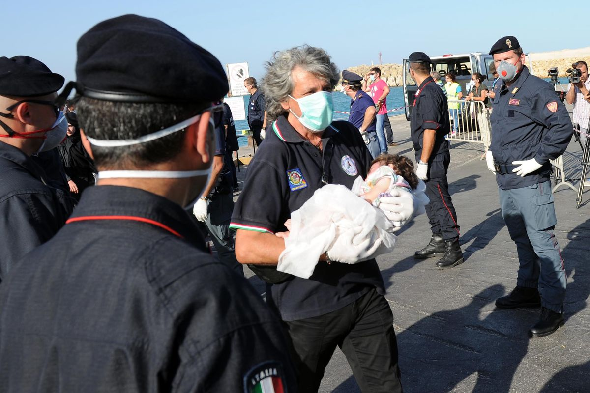 An Italian rescue worker carries a baby who was rescued from a boat carrying unauthorized immigrants to Europe. The EU has proven unable to mount a comprehensive humanitarian response to the Mediterranean migrant crisis, highlighting deeper problems.