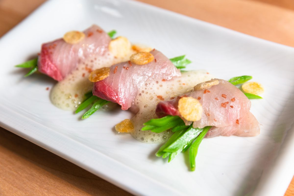 Three pieces of raw fish plated on a white dish