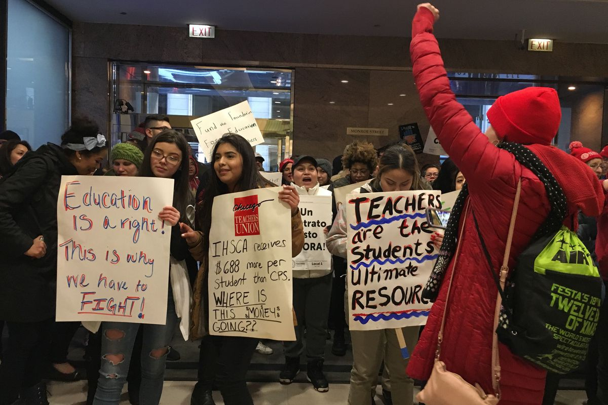 Teachers and students stand in the lobby of a building where their network is holding a board meeting.