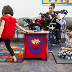 Carla Montilla, back, watches as her children America, 4, left, Nicholas, 8, and Karla, 6, play in the waiting room of the Salt Lake County Health Department WIC Clinic in West Jordan, Tuesday, July 14, 2015. The Salt Lake County Health Department broke ground this morning for the new public health center that will accommodate the growing demand for health services.