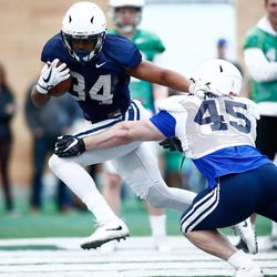 BYU running back Riley Burt (34) runs with the ball as linebacker Martin Barre tries to make the tackle during the Cougars' practice in the Indoor Practice Facility on Thursday, March 15, 2018, in Provo.