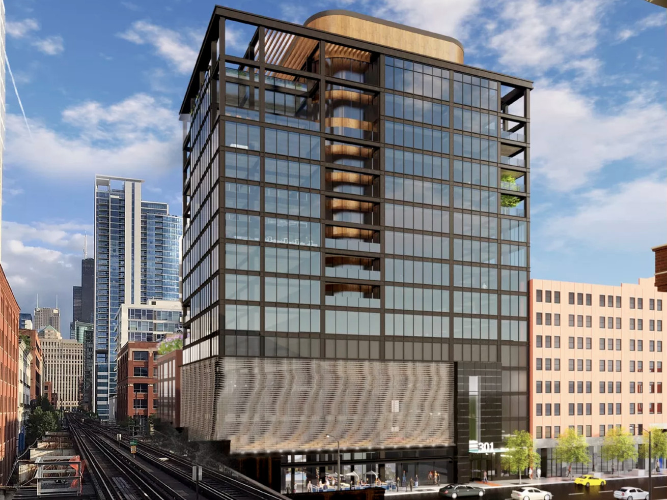 A 15-story office tower rises next to elevated train tracks. The building has a black metal frame with multiple balcony cutouts and an undulating mesh screen at its base.