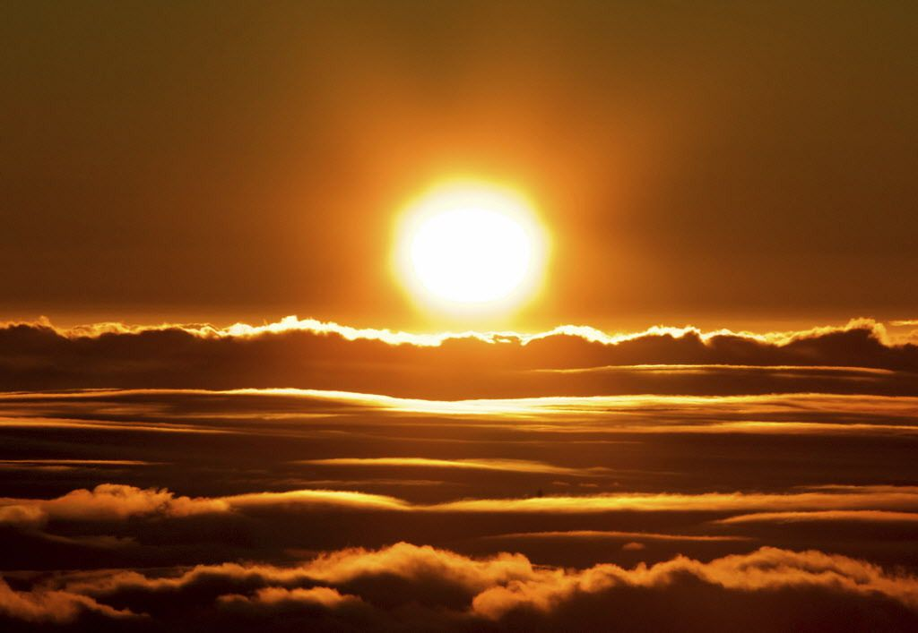 The sun rises over the clouds in front of the summit of Haleakala volcano in Haleakala National Park on Hawaii's island of Maui, Sunday, Jan. 22, 2017. Park officials say the sunrise on Haleakala attracts over a thousand people a day, resulting in an over