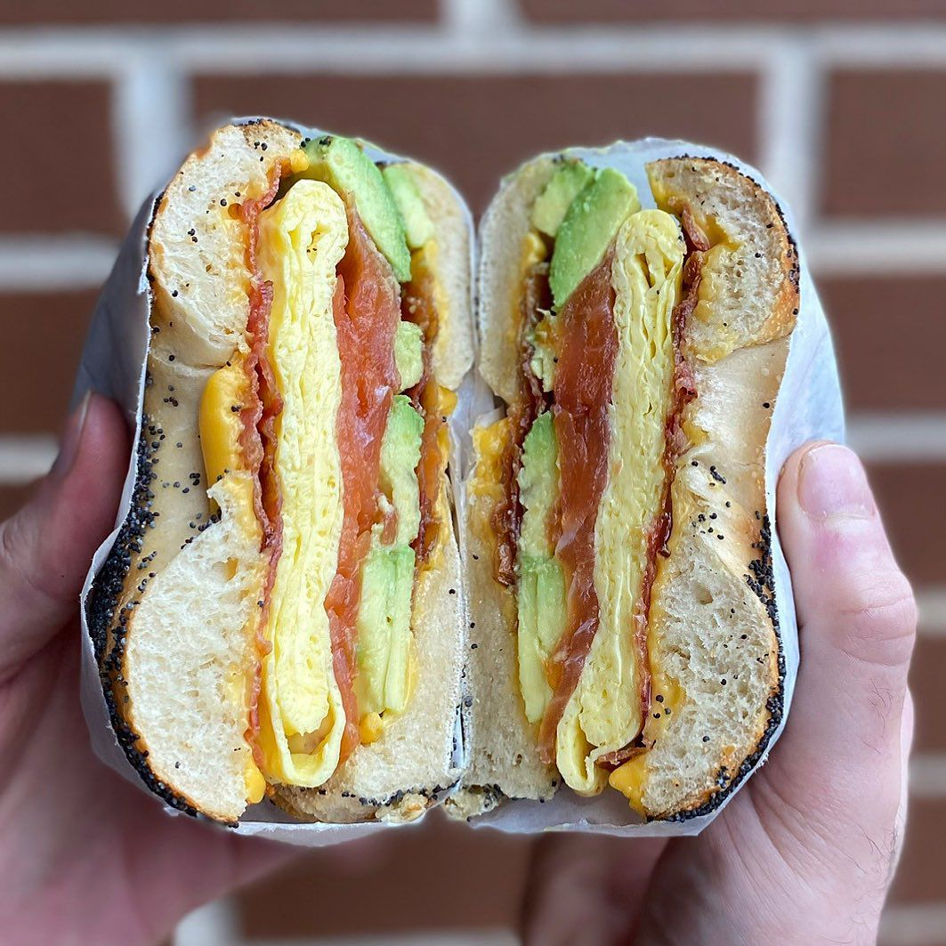 Sesame seed bagel sandwich cut in half containing folded egg, cheddar cheese, bacon, tomato, and avocado held by a pair of hands