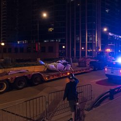 A flatbed truck drives on Roosevelt Rd away from Grant Park with the Christopher Columbus statue loaded onto it after crews removed it from its original location, Friday, July 24, 2020.
