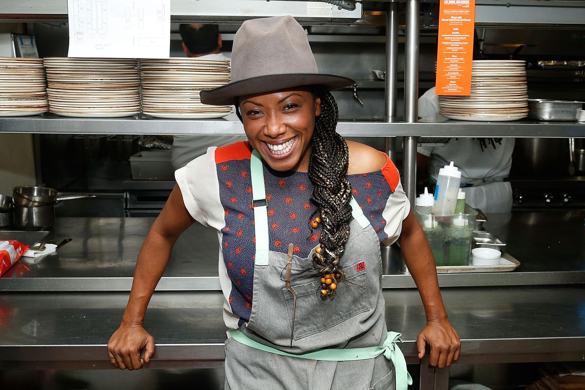 Nyesha Arrington wears a gray hat and gray apron as she poses in a professional kitchen in front of a shelf with stacks of plates. To the right there are bottles for condiments.