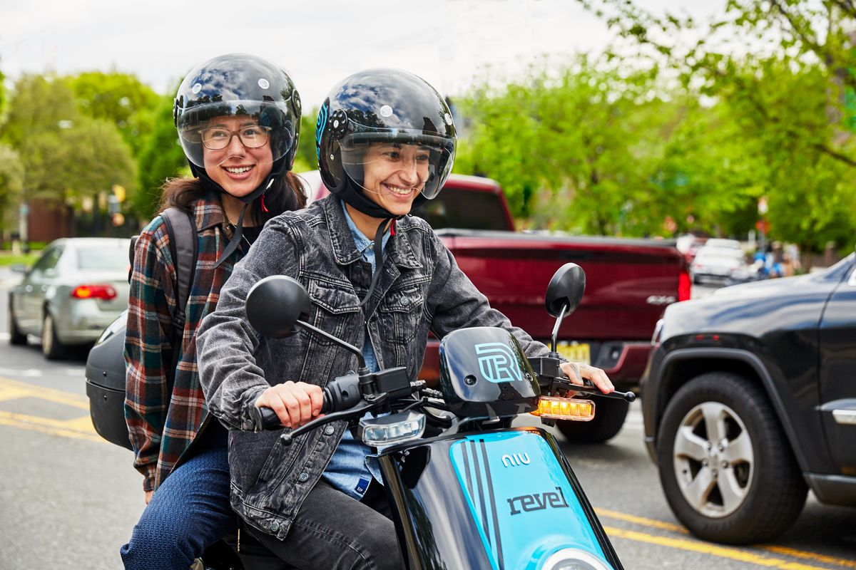 """Two smiling young people in helmets riding an electric moped with the word """"Revel"""" on the front."""