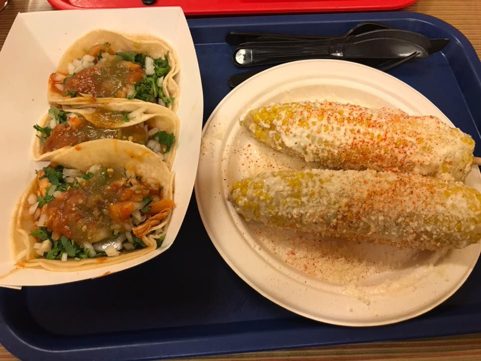 A dimly lit tray of street tacos in a paper boat and two elotes on a paper plate