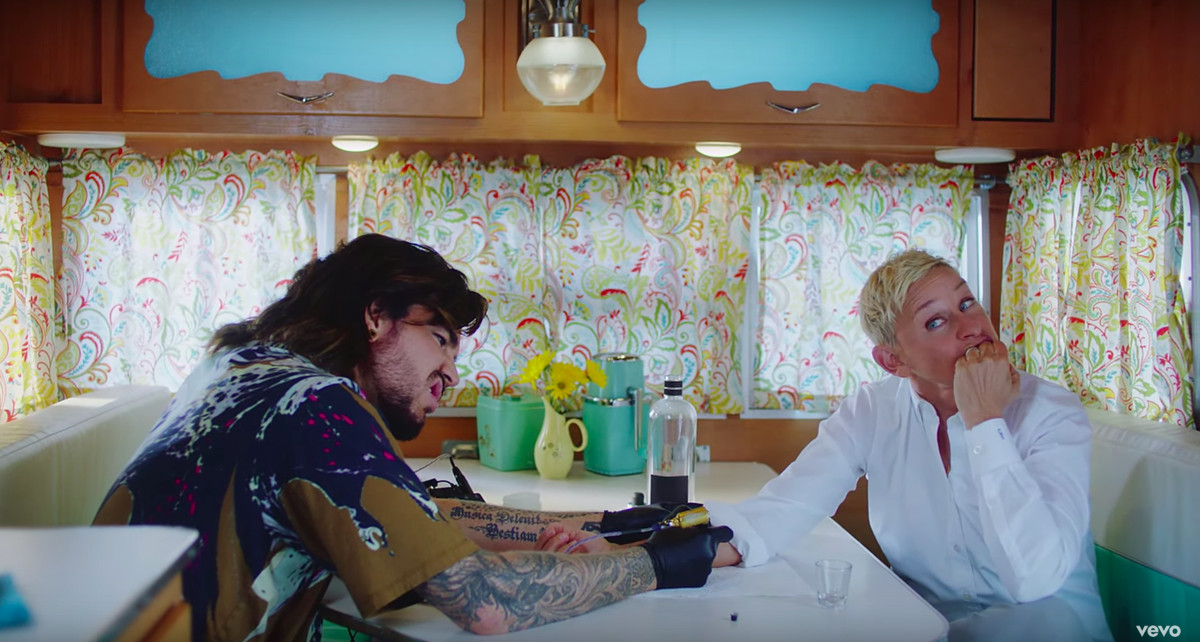 Lambert tattoos DeGeneres's arm at a kitchen table.