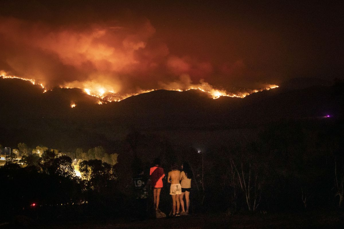 Local residents watch as fire burns to the suburban fringe of the city of Canberra on January 31, 2020, in Canberra, Australia