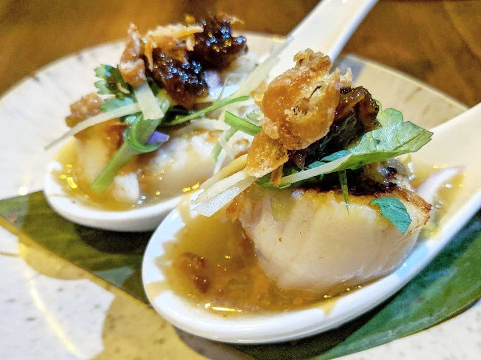 Two white Chinese-style soup spoons each hold a single seared scallop topped with a pile of caramelized duck, crispy shallots, and herbs.