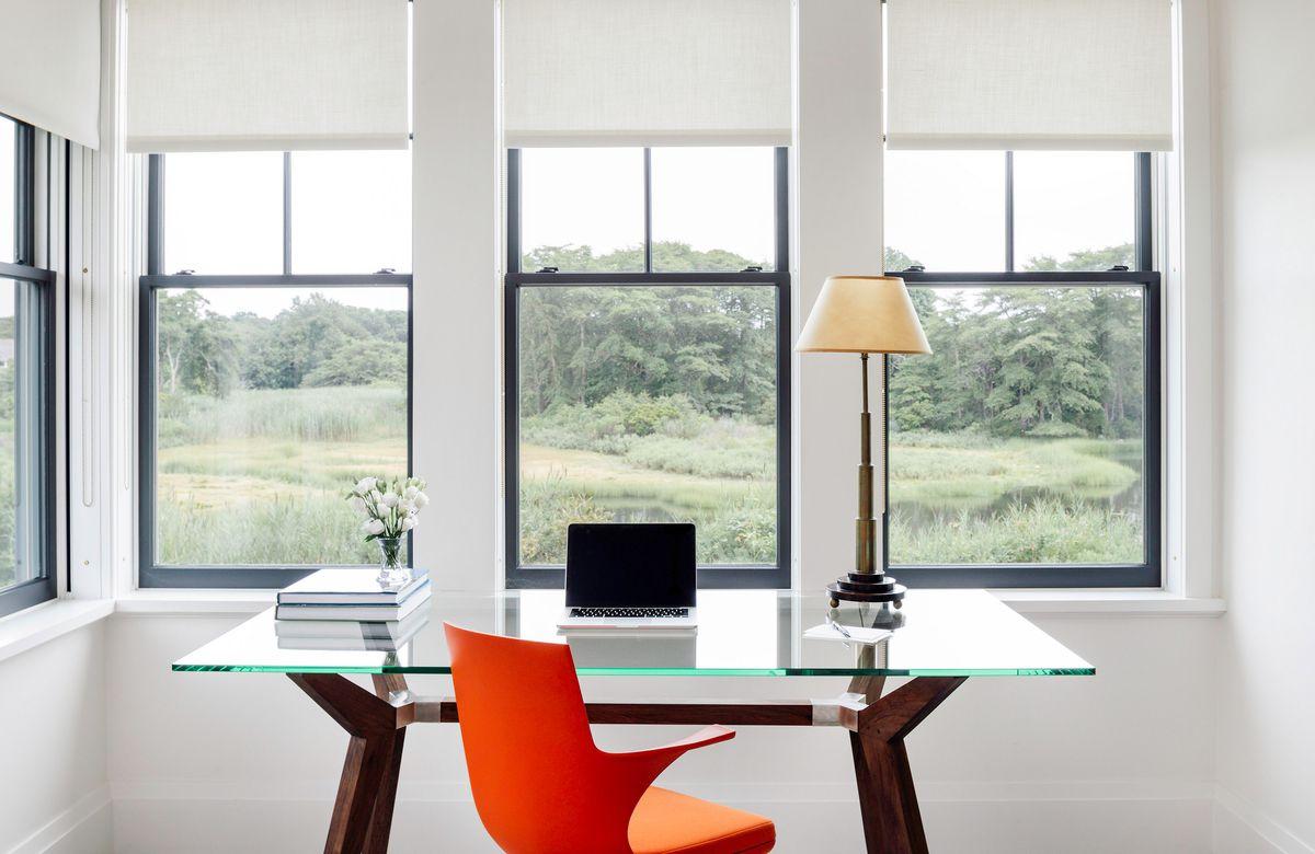 A modern, glass-topped desk has an orange desk chair.