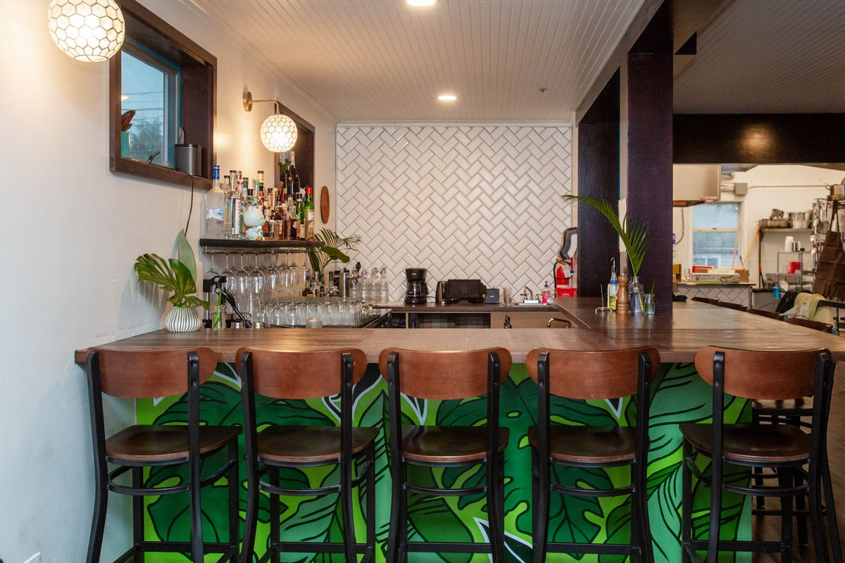 A view of the Musang bar, with a leafy green mural at the bottom and a white tile wall in back.