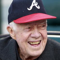 Former United States President Jimmy Carter smiles before a baseball game between the Atlanta Braves and the Milwaukee Brewers in Atlanta, Friday, April 13, 2012.