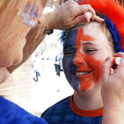 Boise State fan Jacob Oswald has his face painted by his mother Renae before the Boise State vs Brigham Young University football game in Boise, Thursday, Sept. 20, 2012.