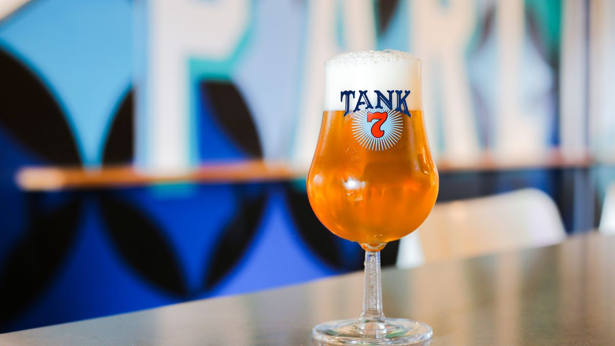 A tulip glass filled with beer, with the Boulevard Brewing Co.'s Tank 7 branding, sits on the bar at Parlor restaurant in Kansas City, with a colorful blue mural in the background.