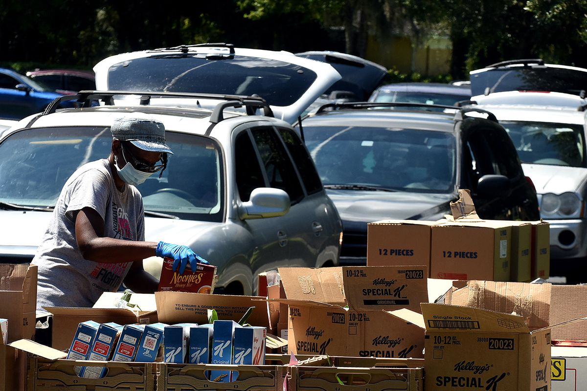 A food bank distribution worker loads boxes beside a line of cars.