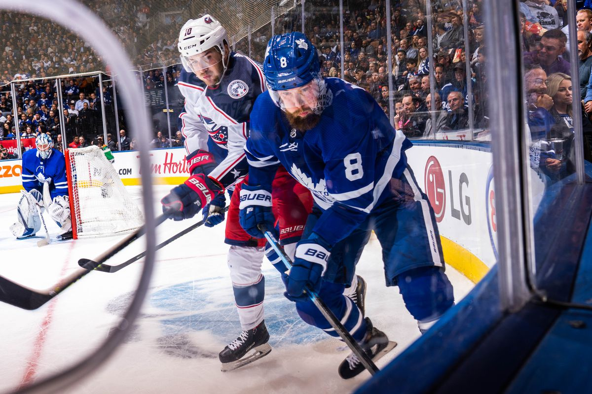 Jake Muzzin of the Toronto Maple Leafs battles with Alexander Wennberg of the Columbus Blue Jackets during the second period at the Scotiabank Arena on October 21, 2019 in Toronto, Ontario, Canada.